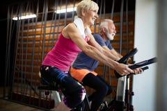 Pares aptos maduros que ejercitan en gimnasio para permanecer sano fotos de archivo libres de regalías