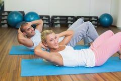 Pares aptos que hacen crujidos abdominales en el gimnasio Fotos de archivo libres de regalías