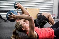 Pares aptos que hacen ejercicio abdominal de la bola Imagenes de archivo