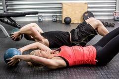 Pares aptos que hacen ejercicio abdominal de la bola Fotografía de archivo