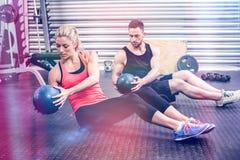 Pares aptos que hacen ejercicio abdominal de la bola Fotos de archivo