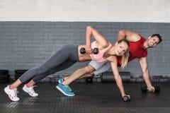 Pares aptos que hacen filas de la pesa de gimnasia Imagen de archivo libre de regalías