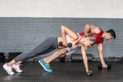 Pares aptos que hacen filas de la pesa de gimnasia Fotos de archivo