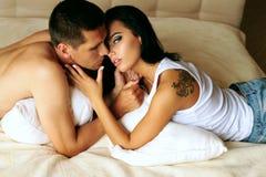 Pares ardentes bonitos 'sexy' que relaxam na cama no hotel Imagem de Stock
