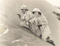 Pares armados que escalam acima a duna de areia Imagens de Stock
