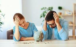 Pares arruinados de la familia de la planificación financiera en la tensión con la hucha imagenes de archivo