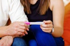 Pares asentados abajo, llevando a cabo la prueba casera del embarazo entre ellos, concepto embarazada imagen de archivo libre de regalías
