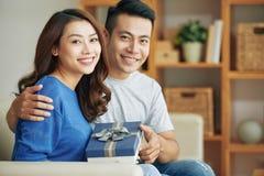 Pares asiáticos alegres que sentam-se com caixa de presente imagem de stock