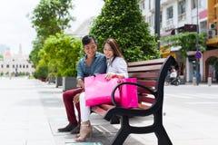 Pares asiáticos após a compra de assento do banco da loja Imagens de Stock