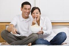 Pares asiáticos atractivos que comen las palomitas en cama Fotos de archivo libres de regalías