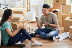 Pares asiáticos com as canecas que conversam no apartamento novo foto de stock royalty free