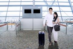 Pares asiáticos com a mala de viagem que sorri no terminal de aeroporto fotografia de stock royalty free