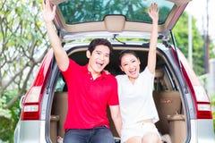 Pares asiáticos com seu carro novo que é entusiasmado fotos de stock