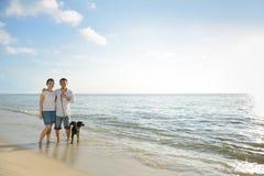 Pares con el perro en la playa Foto de archivo libre de regalías