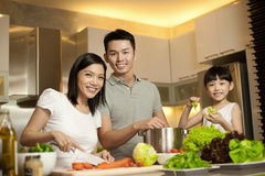 Pares asiáticos con su hija en la cocina foto de archivo libre de regalías