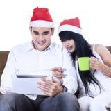 Pares asiáticos de la Navidad que hacen compras en línea Foto de archivo
