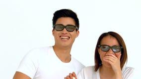 Pares asiáticos de risa que comen las palomitas y que llevan los vidrios de la película metrajes