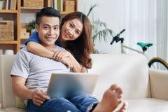 Pares asiáticos de sorriso com o portátil no sofá fotos de stock royalty free