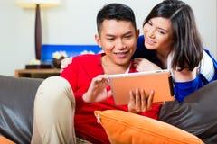 Pares asiáticos en el sofá con una PC de la tableta Imágenes de archivo libres de regalías
