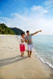 Pares asiáticos felices que recorren a lo largo de la playa Imágenes de archivo libres de regalías