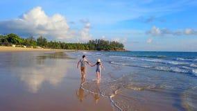 Pares asiáticos felizes que datam na praia durante a viagem da lua de mel do curso em férias dos feriados fora Oceano ou mar da n fotografia de stock