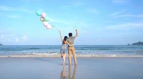 Pares asiáticos felizes que guardam balões coloridos na praia durante a viagem do curso no ar livre das férias dos feriados no oc foto de stock