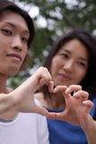 Pares asiáticos hermosos exteriores formando un corazón imagen de archivo libre de regalías