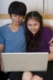 Pares asiáticos jovenes con el ordenador Imágenes de archivo libres de regalías