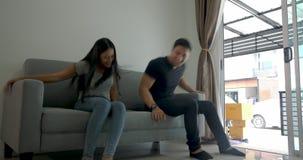 Pares asiáticos jovenes felices que se trasladan un sofá al nuevo apartamento almacen de video