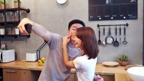Pares asiáticos jovenes felices usando el smartphone para el selfie mientras que cocina en la cocina en casa Hombre y mujer que p almacen de metraje de vídeo