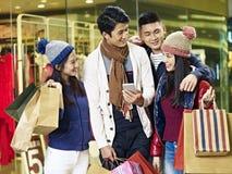 Pares asiáticos jovenes que disfrutan de hacer compras en alameda fotografía de archivo