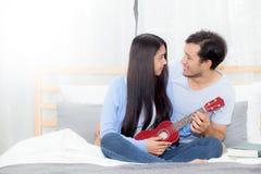 Pares asiáticos jovenes que juegan el ukelele que se relaja con felicidad Imagen de archivo libre de regalías