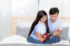Pares asiáticos jovenes que juegan el ukelele que se relaja con felicidad Fotos de archivo libres de regalías