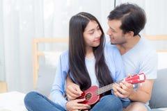 Pares asiáticos jovenes que juegan el ukelele que se relaja con felicidad y alegre Foto de archivo libre de regalías