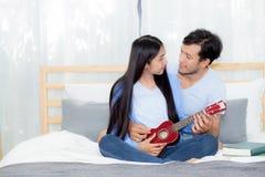 Pares asiáticos jovenes que juegan el ukelele que se relaja con felicidad y alegre Fotos de archivo libres de regalías