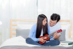 Pares asiáticos jovenes que juegan el ukelele que se relaja con felicidad y alegre en dormitorio Imagen de archivo