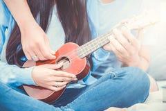 Pares asiáticos jovenes que juegan el ukelele que se relaja con felicidad y alegre en dormitorio Fotos de archivo libres de regalías