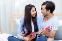 Pares asiáticos jovenes que juegan el ukelele que se relaja con felicidad y alegre en dormitorio Fotografía de archivo
