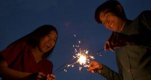 Pares asiáticos jovenes que juegan los fuegos artificiales juntos en el tejado metrajes
