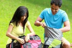 Pares asiáticos jovenes que se preparan a hacer excursionismo Imagen de archivo libre de regalías