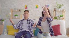 Pares asiáticos jovenes que se sientan en billetes de banco de papel de cogida del sofá metrajes