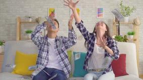 Pares asiáticos jovenes que se sientan en los billetes de banco de papel de cogida MES lento del sofá almacen de metraje de vídeo