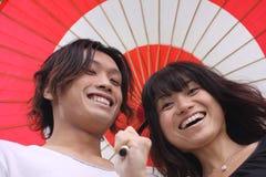 Pares asiáticos jovenes que sonríen con el paraguas imágenes de archivo libres de regalías