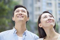 Pares asiáticos jovenes que sonríen y que anticipan al aire libre en jardín Imágenes de archivo libres de regalías