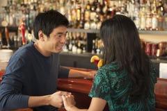 Pares asiáticos jovenes que tienen bebidas Foto de archivo libre de regalías