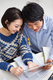 Pares asiáticos jovenes usando la PC de la pista Foto de archivo libre de regalías