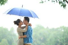Pares asiáticos loving na chuva sob o guarda-chuva imagem de stock royalty free
