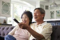 Pares asiáticos mayores en casa en Sofa Watching TV junto Foto de archivo libre de regalías