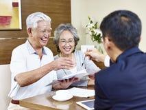 Pares asiáticos mayores listos para firmar el contrato fotografía de archivo libre de regalías