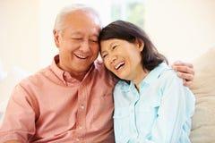 Pares asiáticos mayores que se sientan en Sofa At Home Together Fotos de archivo
